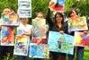 Malen in der Natur, fröhliche Malworkshopteilnehmer zeigen ihre neuen Acryl-Gemälde im Ateliergarten der Kunstschule Atelier Irene Schuh