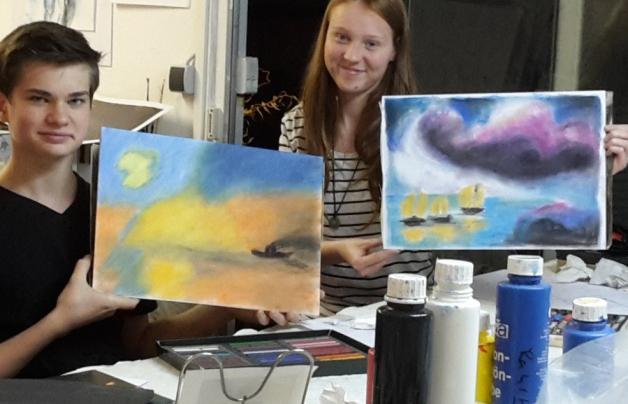 Landschaft mit Pastellkreide zeichnen lernen Glückliche Jugendliche zeigen Ihre wunderschöne Pastellkreide-Zeichnung