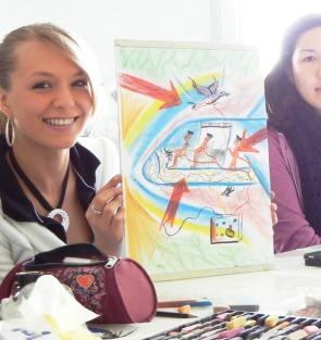 2 glückliche junge Frauen mit einer Entwurfs-Zeichnung im Mappenkurs in der Kunstschule Frankfurt Atelier Irene Schuh